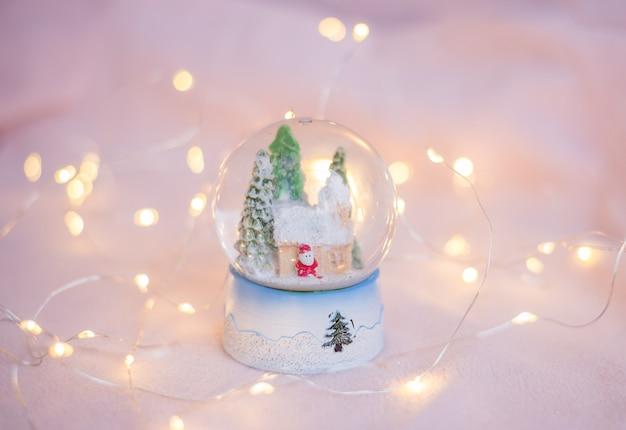 Geschenkschneekugelandenken auf einer hellrosa oberfläche mit weihnachtslichtern