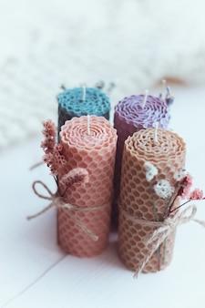 Geschenkset aus vier farbigen dekorativen natürlichen bienenwachskerzen mit getrockneten blüten und honigaroma