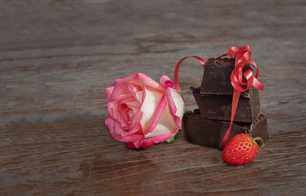 Geschenkset blume, schokolade und erdbeere. rose und schokoladenstücke mit beeren auf einem hölzernen hintergrund.