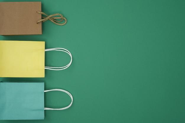 Geschenktüten auf grünem hintergrund kopieren sie den raum flach, indem sie die draufsicht nachahmen