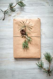 Geschenkverpackung für ein buch oder einen laptop in bastelpapier, gebunden mit einem schnurseil und verziert mit einem tannenzweig mit einem kegel. weihnachtsgeschenke auf dem hölzernen hintergrund