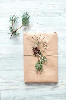 Geschenkverpackung für ein buch oder einen laptop in bastelpapier, gebunden mit einem schnurseil und verziert mit einem tannenzweig mit einem kegel