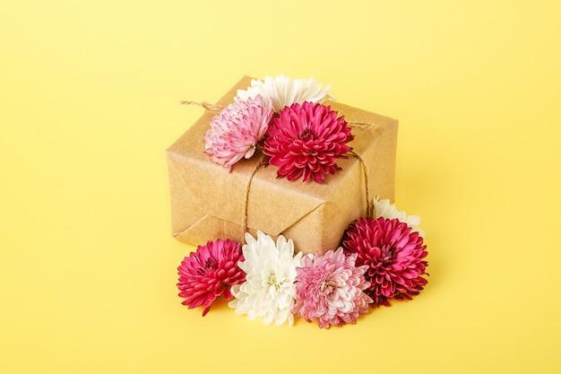 Geschenkverpackung im eco zero waste-stil. komposition mit geschenkpapier-geschenkbox, verziert mit blumen