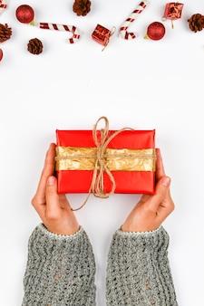 Geschenkverpackung in rot und gold in den händen. mit einer schleife auf einem weißen raum gestrickt. diy geschenkverpackung. frauenhände geben ein verpacktes geschenk. weihnachtsgeschenk. sicht von oben.