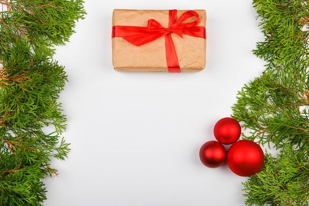 Geschenkverpackung mit einer roten schleife auf einem weißen raum. nadelgrüne zweige auf einem weißen raum