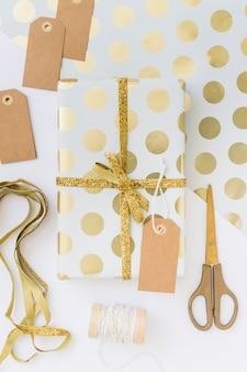 Geschenkverpackung mit etikett in der nähe von schere und klebeband