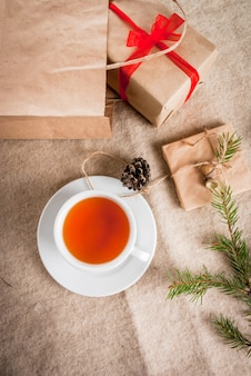 Geschenkverpackung und briefe, karten für weihnachtsgrüße. umschläge mit briefen, geschenken, christbaumzweigen und tannenzapfen liegen auf einer holztischlüge, eine tasse duftenden heißen tees, draufsicht