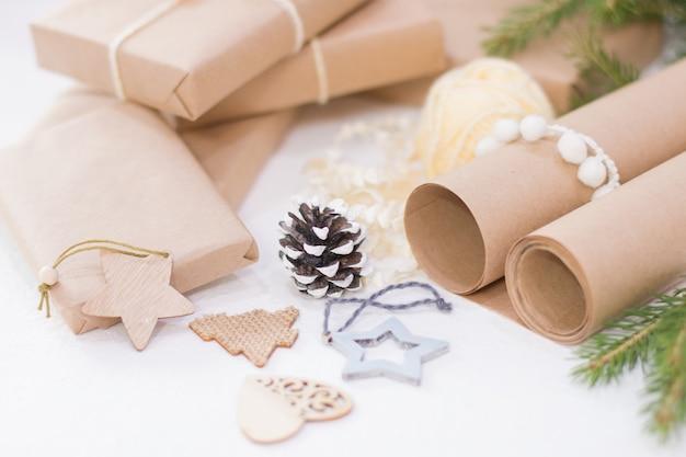 Geschenkverpackungsprozess für weihnachten und neujahr, umweltfreundliche geschenkboxen und natürliches weihnachtsdekor auf weißem tisch, fokus auf tannenzapfen, gemütliches werkstattkonzept