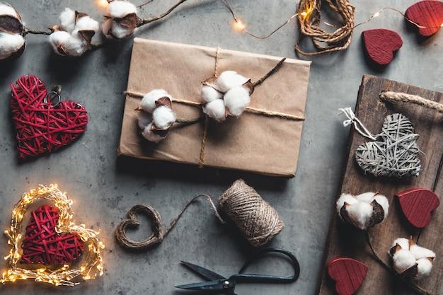 Geschenkverpackungszubehör. geschenke in bastelpapier auf grauem hintergrund. valentinstag, überraschung und baumwollblumen