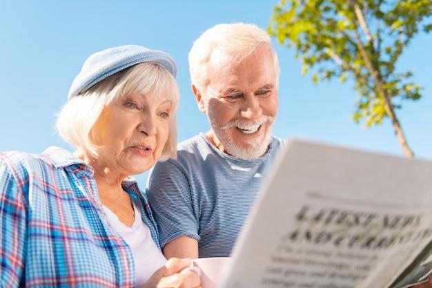 Geschichte sehen. großmutter und großvater freuen sich, die geschichte über ihre enkelkinder in einer zeitung zu sehen