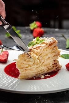 Geschichtete gebackene torte mit cremiger vanillecreme, äpfeln und erdbeermarmelade, dekoriert mit minze. vertikales bild. ansicht von oben. platz für text.