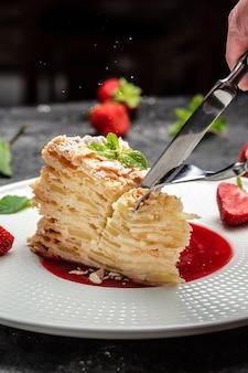 Geschichtete gebackene torte mit cremiger vanillecreme, äpfeln und erdbeermarmelade