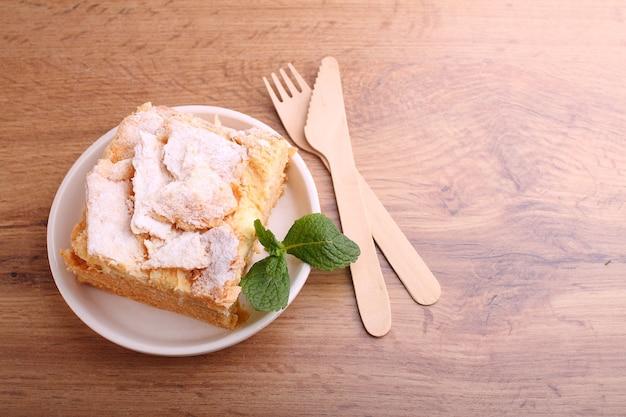 Geschichteter kuchen napoleon mit vanillemilchcremescheibe verziert mit minze, auf einem teller auf einem hölzernen hintergrund.