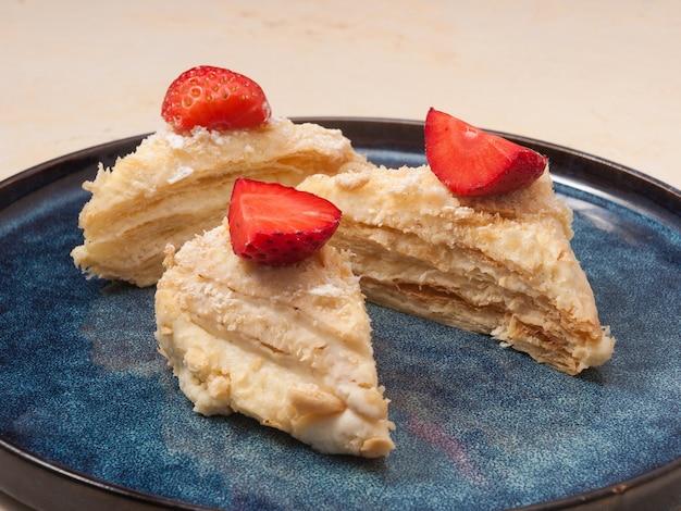 Geschichteter napoleon-kuchen, verziert mit erdbeeren auf einem blauen teller in einem restaurant