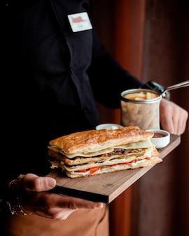 Geschichtetes sandwich mit blätterteig, serviert mit pommes frites und sauce