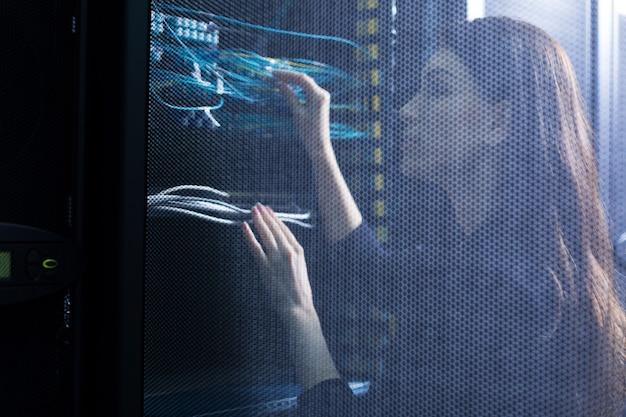 Geschickte erfahrene ingenieurin, die sich die internetkabel ansieht und ihre arbeit überprüft, während sie im serverraum arbeitet