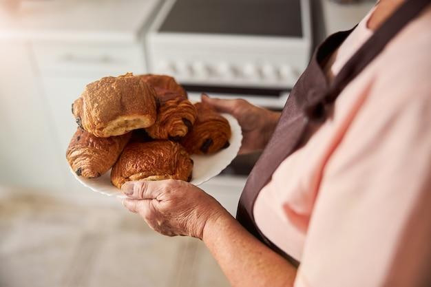 Geschickte großmutter, die frisches gebäck zum abendessen bereithält