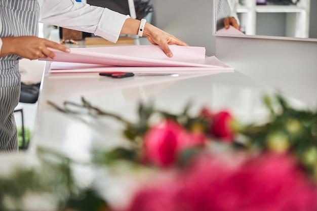 Geschickte hände eines blumenladenarbeiters, der geschenkpapier berührt