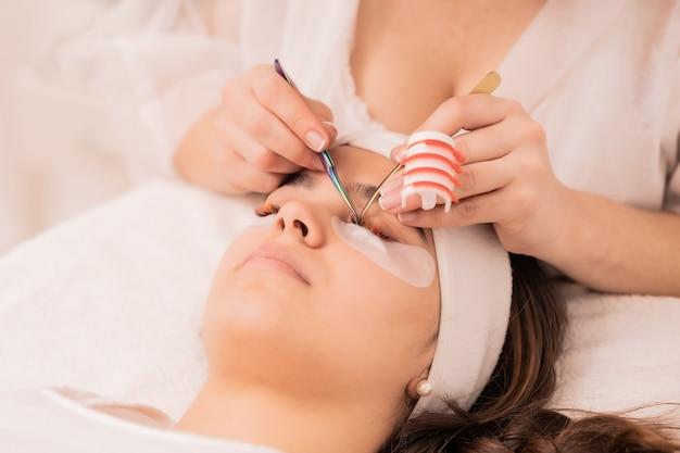 Geschickte kosmetikerin, die das verfahren zur wimpernverlängerung durchführt - beauty-konzept