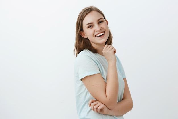 Geschickte kreative und ehrgeizige europäische frau im trendigen t-shirt, das im profil über weißer wand steht, die mit zufriedenem glücklichem und selbstbewusstem lächeln hand in hand am kinn dreht