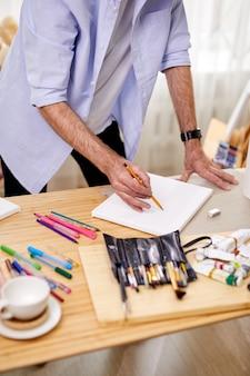 Geschickte malerzeichnung skizze auf blatt mit bleistift, werkzeug und materialien auf tisch, im kunststudio, arbeitsprozess, allein