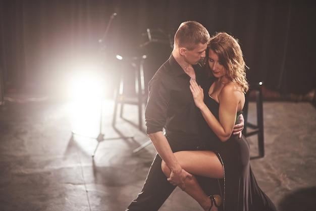 Geschickte tänzer, die in einem dunklen raum unter licht auftreten.