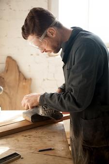 Geschickter junger tischler, der holzarbeiten herstellt, mit elektrischem schleifer arbeitet, vertikal