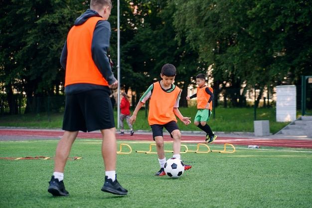 Geschickter spieler in fußballuniform, der mit seinem trainer auf dem sportplatz trainiert