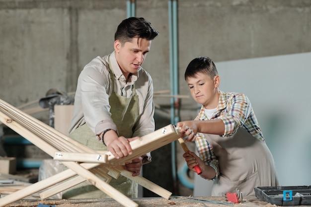 Geschickter teenager in der schürze mit hammer während der arbeit an holzmöbeln mit vater in der tischlerei