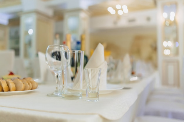Geschirr auf banketttischen, serviergläsern, löffeln und tellern