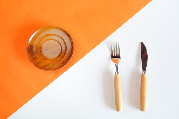 Geschirr auf orange farbe des papiers und des weißen brettes.