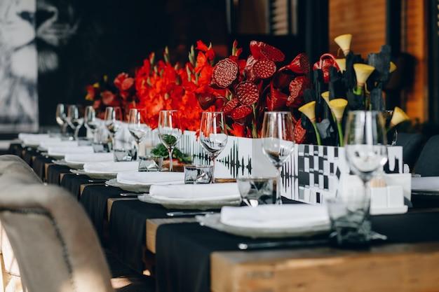 Geschirr gläser, blumengabel, messer zum abendessen im restaurant mit gemütlichem interieur