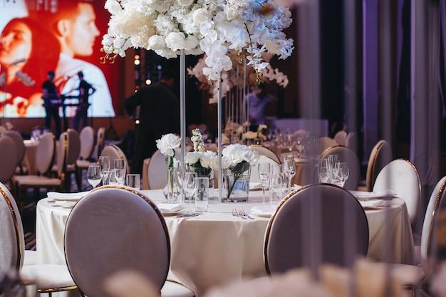 Geschirr gläser blumengabelmesser zum abendessen im restaurant mit gemütlichem interieur serviert