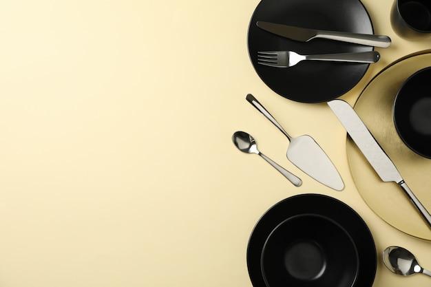 Geschirr und besteck auf beigem hintergrund, draufsicht