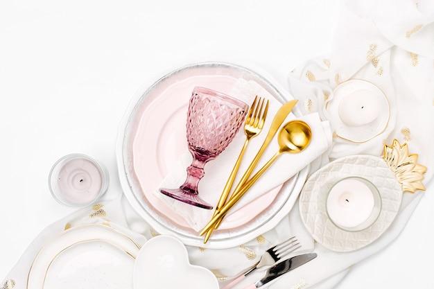 Geschirr und dekorationen zum servieren einer festlichen tafel. teller, weingläser und besteck mit dekorativem textil auf weißem hintergrund.