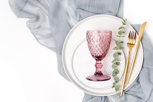 Geschirr und dekorationen zum servieren einer festlichen tafel. teller, weingläser und besteck mit grauem dekorativem textil auf weißem hintergrund. Premium Fotos