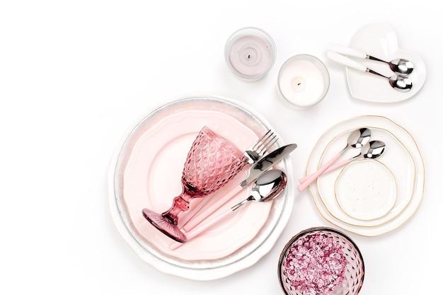 Geschirr und dekorationen zum servieren einer festlichen tafel. teller, weingläser und besteck mit kerzen auf weißem hintergrund.