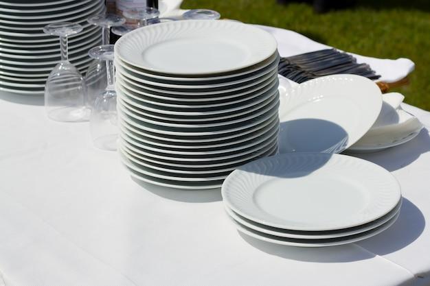 Geschirr und gläser auf weißer serviette