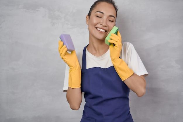 Geschirrspülen mit spaß. glückliche junge putzfrau in gelben gummihandschuhen, die mit küchenschwämmen spielt und lächelt, während sie gegen graue wand steht. studioaufnahme. zimmerreinigung, reinigungsdienste