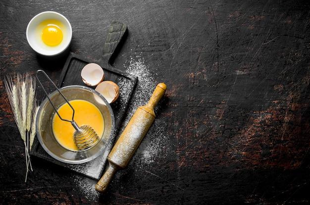 Geschlagene eier in einer glasschüssel mit einem schneebesen auf rustikalem tisch