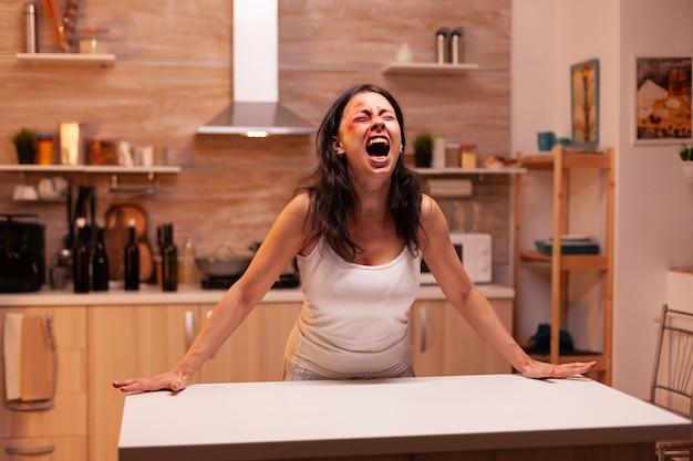 Geschlagene frau schreit in der heimischen küche mit verletztem gesicht wegen gewalttätigem ehemann. gewalttätiger aggressiver ehemann, der verängstigte, hilflose, verletzliche, ängstliche, geschlagene und in panik geratene ehefrau verletzt.