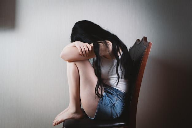 Geschlagene junge frau, die auf einem stuhl sitzt
