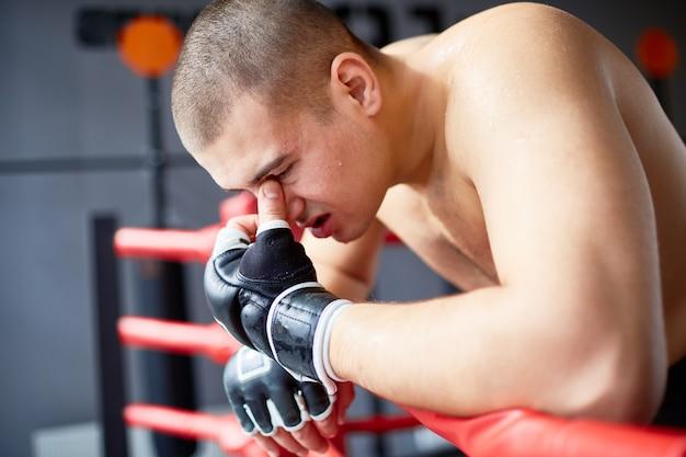 Geschlagener boxer, der auf ring railing sich lehnt