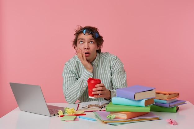 Geschlagener junger dunkler mann mit wilden haaren, der am arbeitstisch sitzt, müde nach oben schaut und eine tasse kaffee in der hand hält, kopf an hand lehnt und brillen auf der stirn hält