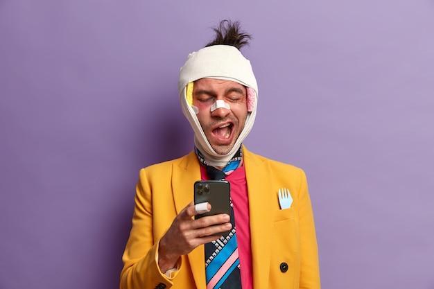 Geschlagener, verletzter mann fühlt sich während der rehabilitationsphase zu hause gelangweilt, benutzt ein smartphone und gähnt mit schläfrigem gesichtsausdruck, verletzt nach einem schweren unfall, in helle kleidung gekleidet, posiert drinnen