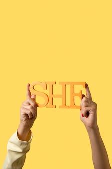 Geschlecht flüssige person, die ein auf gelb isoliertes pronomen hält