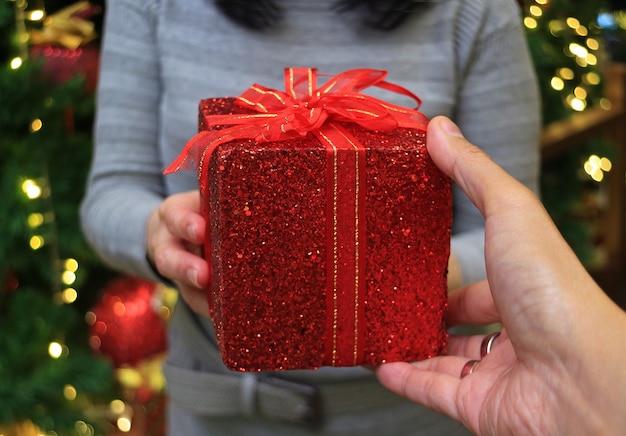 Geschlossen eine hand eines mannes, der rote quadratische geschenkbox hält, die einer frau übergibt