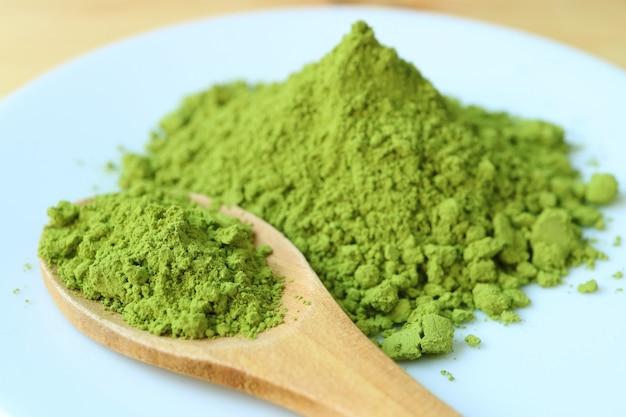 Geschlossen herauf einen löffel vibrierenden grünen matcha-teepulvers auf einer platte mit undeutlichem grünem teepulver-stapel im hintergrund