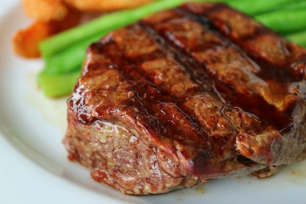 Geschlossen herauf gegrilltes lendenstück-steak mit unscharfem gemüse im hintergrund