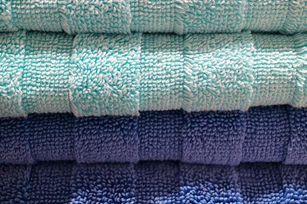 Geschlossen herauf stapel tiefblaue und hellblaue flaumige badetücher, für beschaffenheit und hintergrund